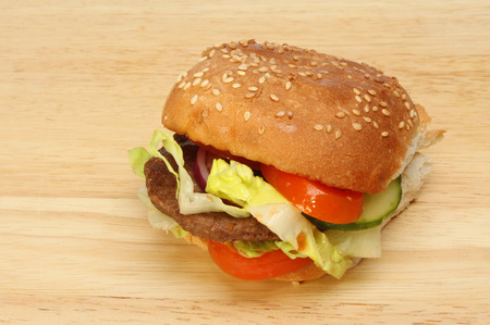 bap: Beef burger with salad in a sesame seeded bap on a wooden board