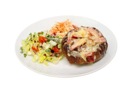 Cheese and bacon baked potato with salad on a plate isolated against white photo