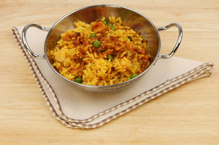 serviette: Lamb biryani in a balti dish with a serviette on a wooden table top Stock Photo