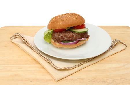 servilleta de papel: Hamburguesa de ternera en un plato con una servilleta en una mesa de madera