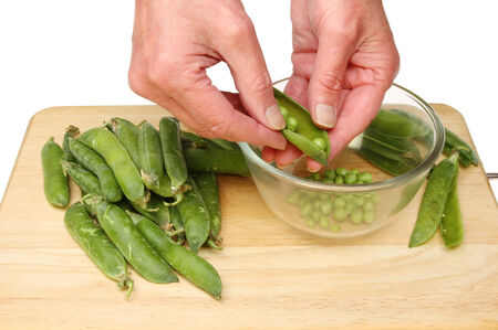 shelling: Closeup of hands shelling peas into a glass bowl on a wooden board