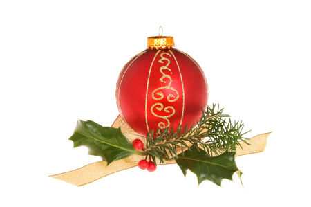 Christmas decoration, red and gold glitter bauble with holly, pine needles and a gold ribbon isolated against white photo