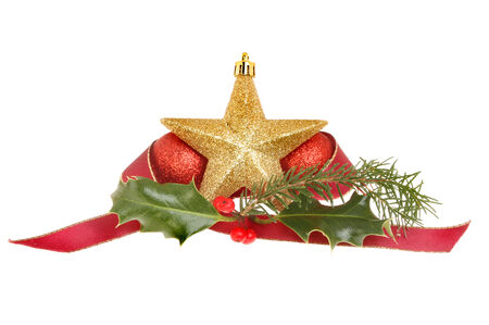 Christmas decoration, gold star with red baubles, pine needles, holly and a red ribbon isolated against white photo