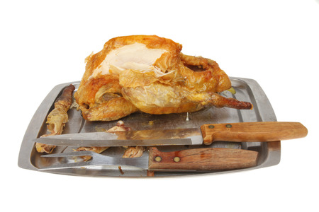 guinea fowl: Part carved Guinea fowl on a carving dish with carving knife and fork isolated against white