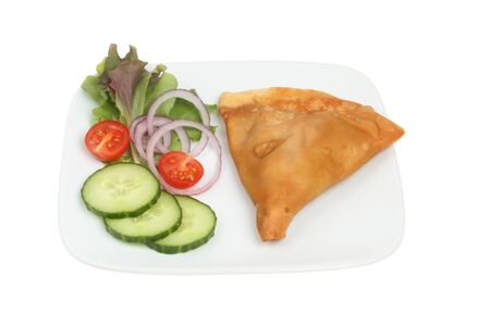 samosa: Samosa and salad on a plate isolated against white