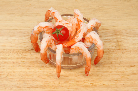 fantail: Fantail prawns with a tomato in a glass dish on a wooden board