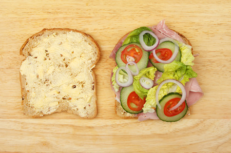 multi grain sandwich: Two halves of a ham salad sandwich on a wooden board Stock Photo