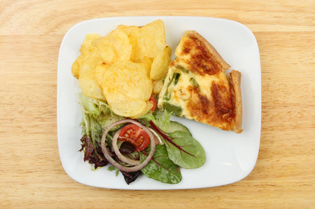 potato crisps: Quiche, salad and potato crisps on a plate on a wooden board Stock Photo