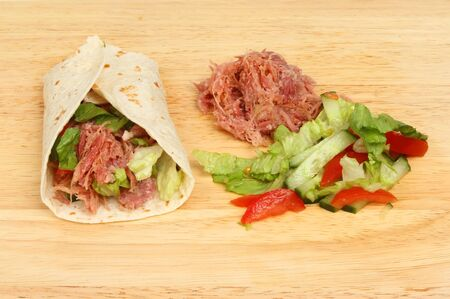 pulled: Pulled pork bread wrap with ingredients on a wooden board Stock Photo