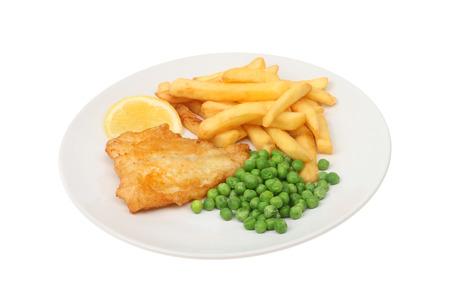 fish and chips: baterred pescado, patatas y guisantes con una rodaja de limón en un plato aislados contra blancos