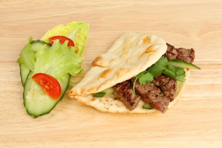 garnish: Flatbread filled with steak cucumber and coriander with a salad garnish on a wooden board