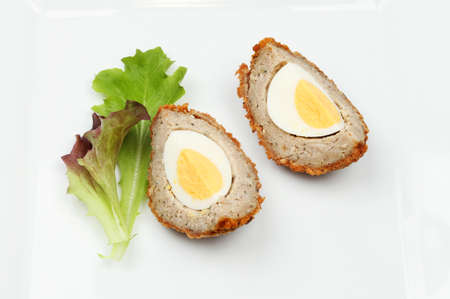 portions: Portions of scotch egg on a plate with lettuce leaves Stock Photo