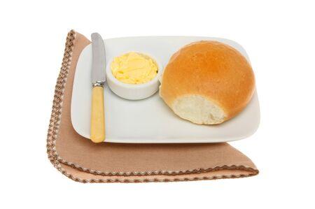 servilleta de papel: rollo de pan crujiente con mantequilla y un cuchillo en un plato con una servilleta aislados contra blancos