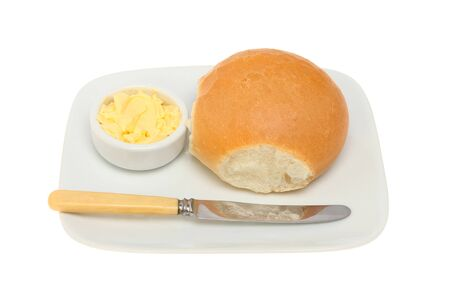 ramekin: Crusty bread roll on a plate with a knife and butter in a ramekin isolated against white Stock Photo