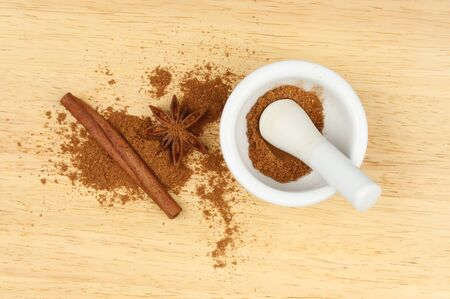 five star: Chinese five spice in a pestle and mortar with star anise and cinnamon on a wooden board Stock Photo