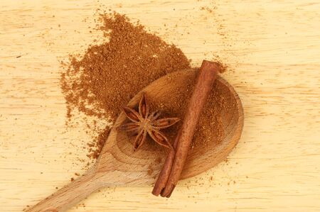 five star: Chinese five spice in a wooden spoon with star anise and cinnamon on a wooden board
