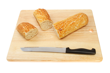 bread knife: Cut Tiger baguette with a bread knife on a bread board isolated against white Stock Photo