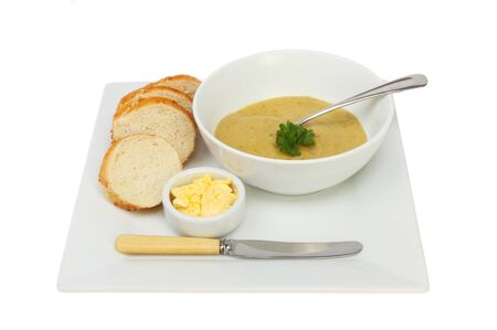 stilton: Brocolli and Stilton soup in a bowl with crusty bread and butter on a plate isolated against white Stock Photo