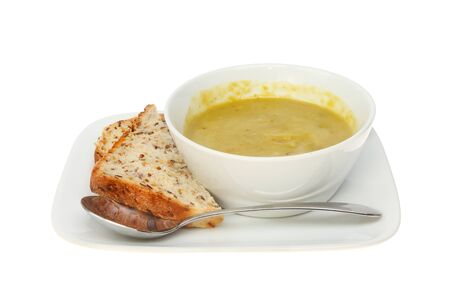 soup bowl: Pea and ham soup in a bowl with soya and linseed bread and a spoon on a plate isolated against white