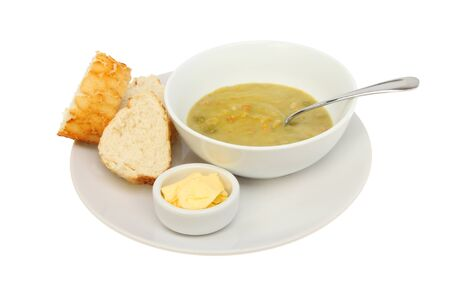 crust crusty: Bowl of pea and ham soup with crusty bread and butter on a plate isolated against white Stock Photo