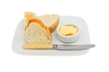 ramekin: Crusty bread with butter in a ramekin and a knife on a plate isolated against white