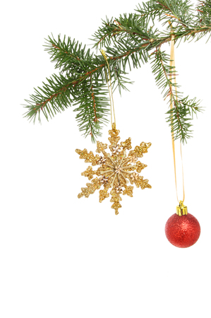 star ornament: Gold glitter Christmas star ornament and red bauble hanging from a conifer branch against a white background Stock Photo