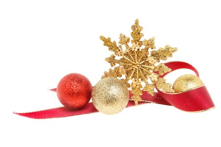 christmas motif: Christmas decoration a gold glitter star with red ribbon and baubles isolated against white