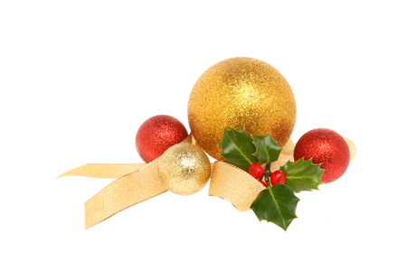christmas motif: Christmas decoration, gold and red baubles with ribbon and Holly isolated against white
