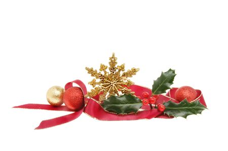 christmas motif: Christmas decoration, red ribbon, gold glitter star, baubles and Holly isolated against white