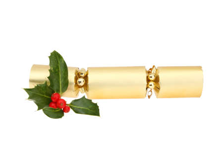 holly: Gold foil Christmas cracker with a sprig of holly isolated against white Stock Photo