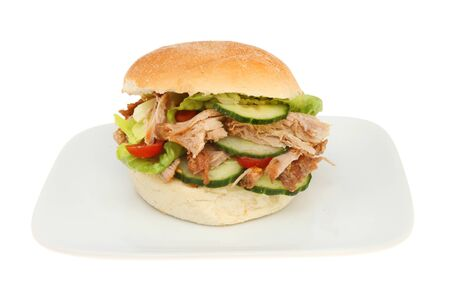 bap: Pulled pork and salad in a soft bread roll on a plate isolated against white Stock Photo