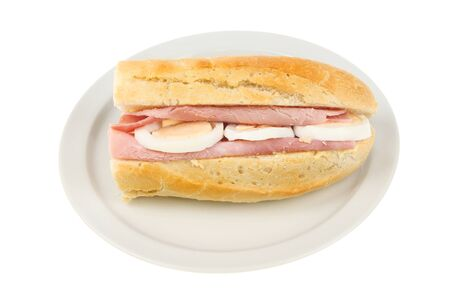 hard boiled: Ham and hard boiled egg baguette on a plate isolated against white