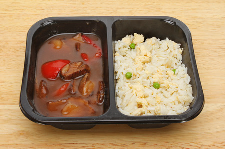 Oriental microwave meal, duck in plum sauce with egg fried rice in a plastic carton on a wooden board