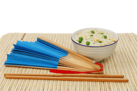 paper fan: Asian meal, egg fried rice in a bowl with chopsticks and a blue paper fan on a bamboo matt against a white background Stock Photo