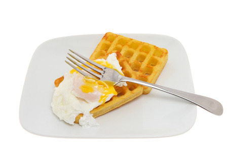 runny: Fork in the runny yolk of a poached egg on potato waffles on a plate isolated against white Stock Photo