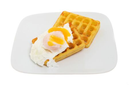runny: Runny yolk poached egg on potato waffles on a plate isolated against white Stock Photo