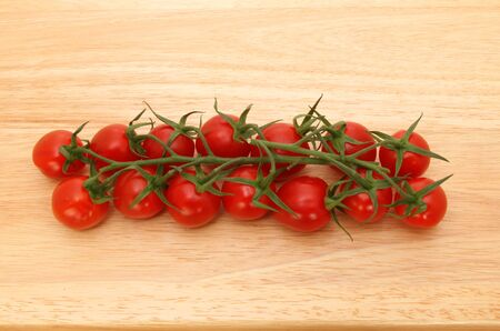 ripened: Vine ripened plum tomatoes on a wooden board Stock Photo