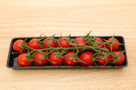 ripened: Vine ripened plum tomatoes in a plastic carton on a wooden board