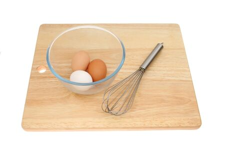 Three eggs in a glass mixing bowl with a whisk on a wooden chopping board isolated against white