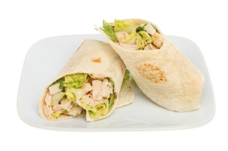 chicken caesar salad: Two chicken Caesar salad sandwich wraps on a plate isolated against white