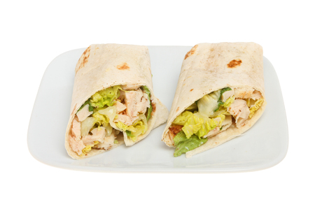 chicken caesar salad: Chicken Caesar salad sandwich wraps on a plate isolated against white