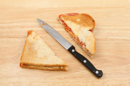 toasted sandwich: Two halves os a toasted sandwich with a knife on a wooden chopping board