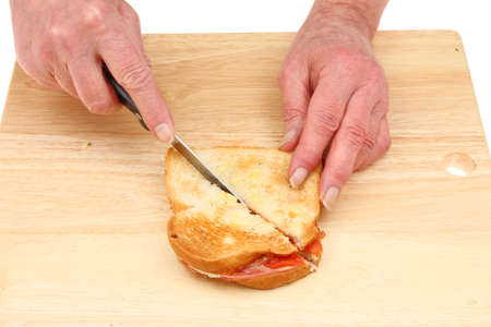 toasted sandwich: Closeup of a pair of hands cutting a toasted sandwich on a wooden chopping board
