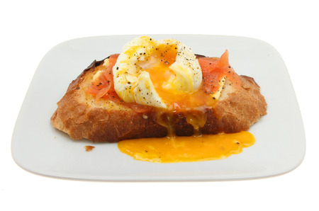 crust crusty: Runny yolk poached egg and smoked salmon on toasted crusty bread on a plate isolated against white Stock Photo