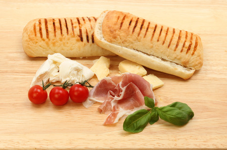 parma ham: Ingredients for a cheese,Parma ham, tomato and basil pannini on a wooden chopping board