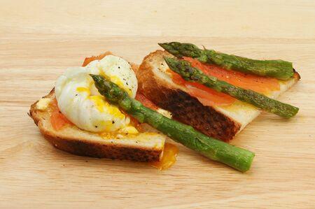 salmon ahumado: salmón ahumado, asaparagus con un huevo escalfado sobre pan crujiente tostado en una tabla de madera