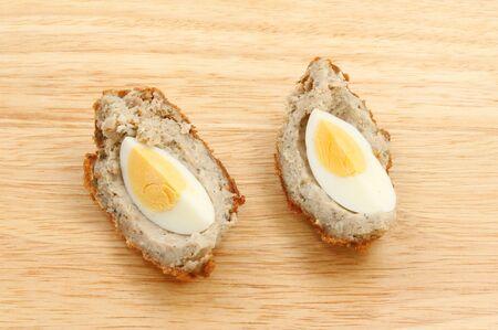 scotch: Scotch egg segments on a wooden chopping board Stock Photo