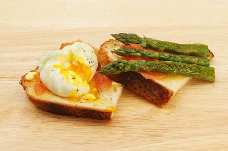 crusty: Smoked salmon with a poached egg and asparagus on toasted crusty bread on a wooden board