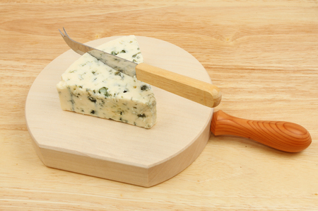 cheese knife: Wedge of Danish blue cheese with a cheese knife on a wooden chopping block Stock Photo