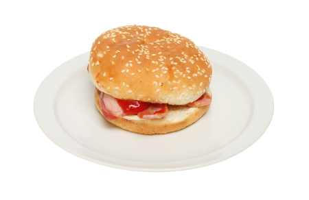bap: Bacon with tomato ketchup in a bap on a plate isolated against white